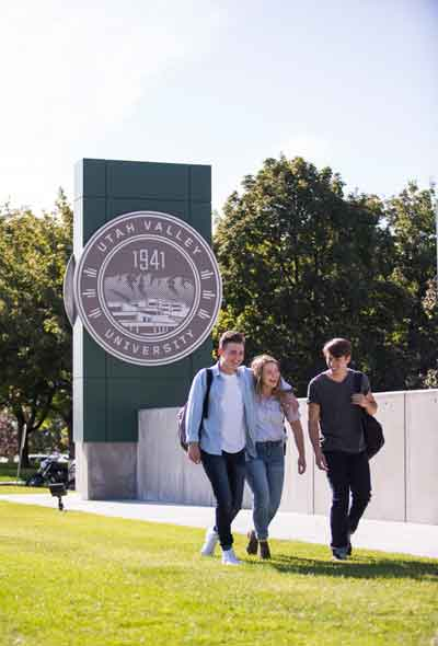 Students walking in front of the UVU seal at the entrance of campus.