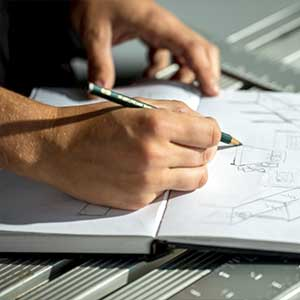A person drawing a building draft