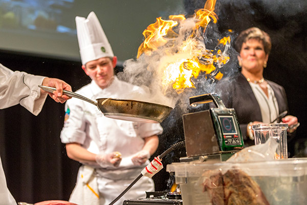 Food ignites in a pan while being flambéed.