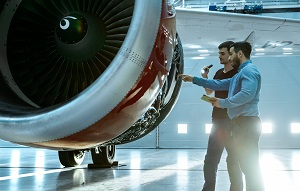 two technicians inspecting a turbofan engine