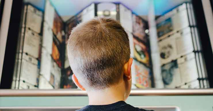 Young boy looking at a shelf with lots of options to choose from pictures.