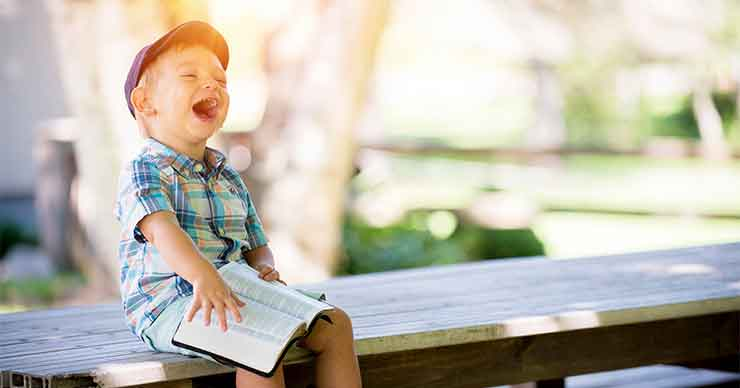 Child laughing heartily while sitting on a bench reading a book