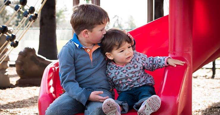 Child intently looking at a mobile device, while sitting at a desk.