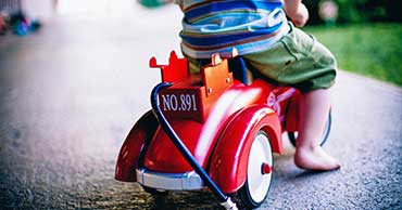 Young child riding a toy fire truck.