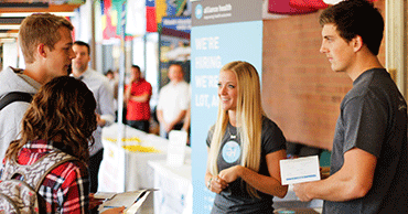 people talking at career fair booth