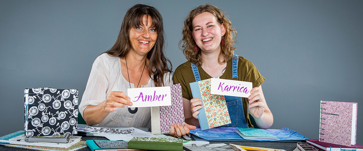 Amber and Karrica showing collection of books