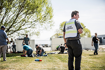 Man directing people around a group of medics giving CPR