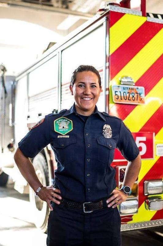 Female EMT standing in front of an ambulance