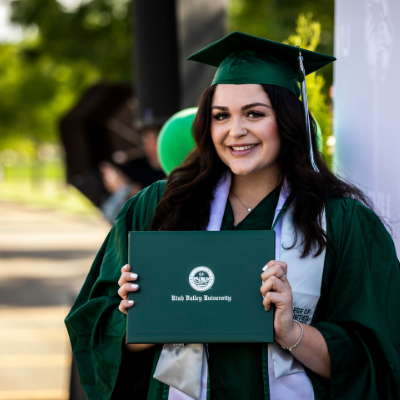 smiling, dark haired female student, in green cap and gown, holding diploma cover