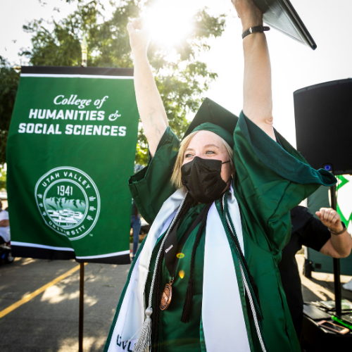female student dressed in green cap and gown, arms raised in triumph