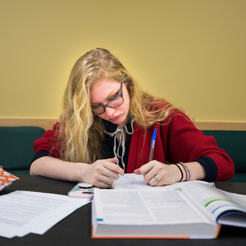 female student studying at a table
