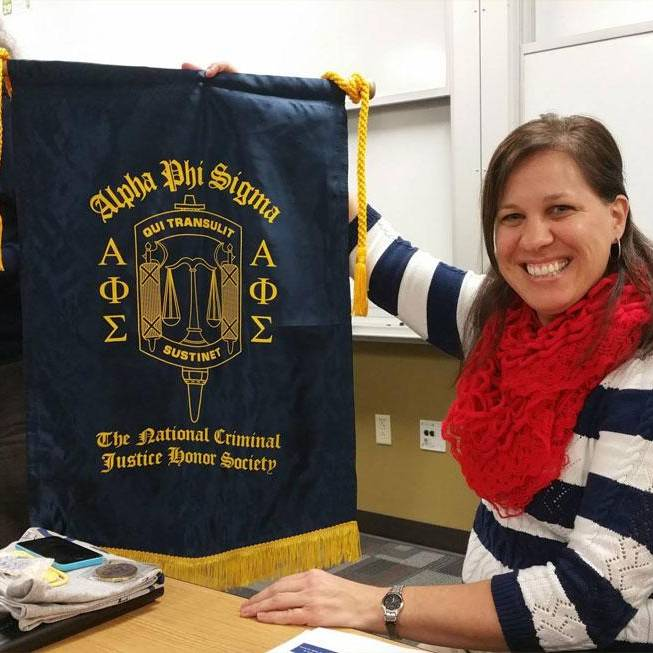 woman holding honor society flag