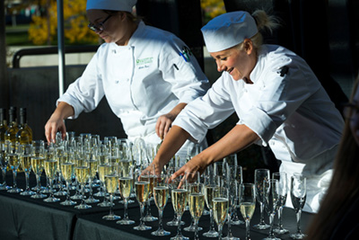 students arranging filled glasses at gala