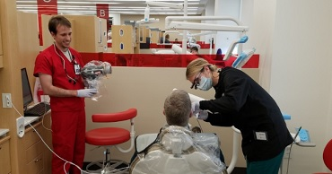 A UVU dental student and a U of U dental student work on a patient