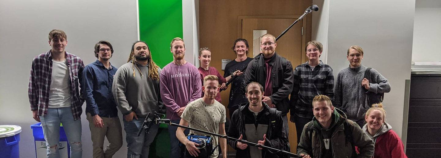 Audio club members on campus with boom poles, microphones, and audio mixer