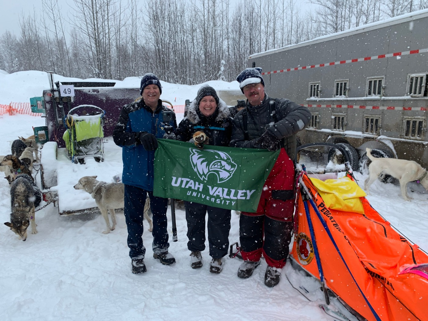 Mike Wisland, Emily Hedrick, and and musher Alan Eischens holding the UVU Flag with sleds and dogs about them.