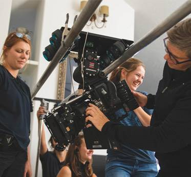 female professional and students adjusting camera on dolly