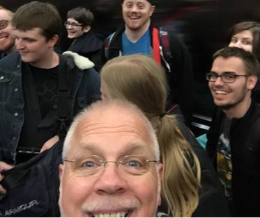 Marty Clayton closeup selfie with UVU students behind him