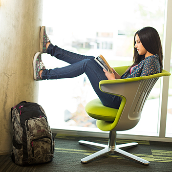 Dark haired female student sitting in a chair with her legs propped up on the wall reading a book