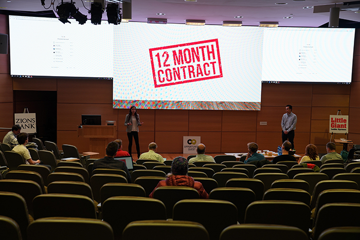 "Alessandra Camargo and Nicolas Camargo standing in front of a large screen reading ""12 month contract"" in red."