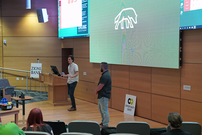 Matt Perry and Brock Hensen standing in front of a screen displaying a white wolf logo on a green background.