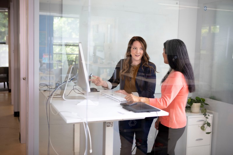 Two women discussing work at a laptop on a standing desk.
