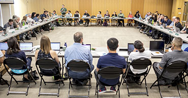 Photo of a Faculty Senate meeting. A large room with tables set in a square with the senate facing inwards towards eachother.