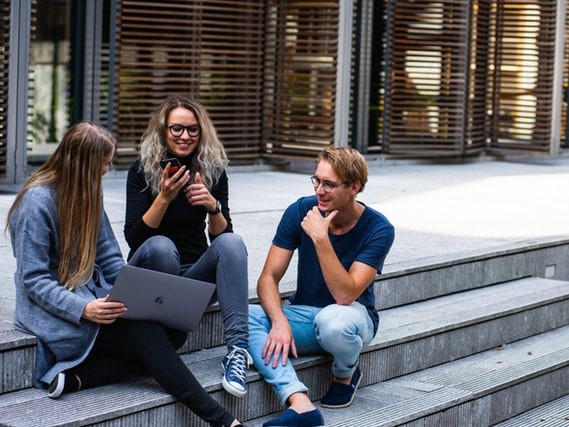 Students talk and laugh outside