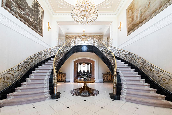 inside photo of Lakemount Manor, featuring a grand double staircase and lavish halls