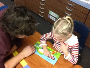Child with instructor reading a book