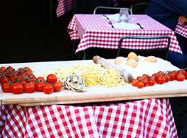 Wood platter with tomatoes, noodles, and eggs.