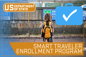 US State Department - Smart Traveler Enrollment Program. Image of Person with backpack on standing in front of sign in a foreign language