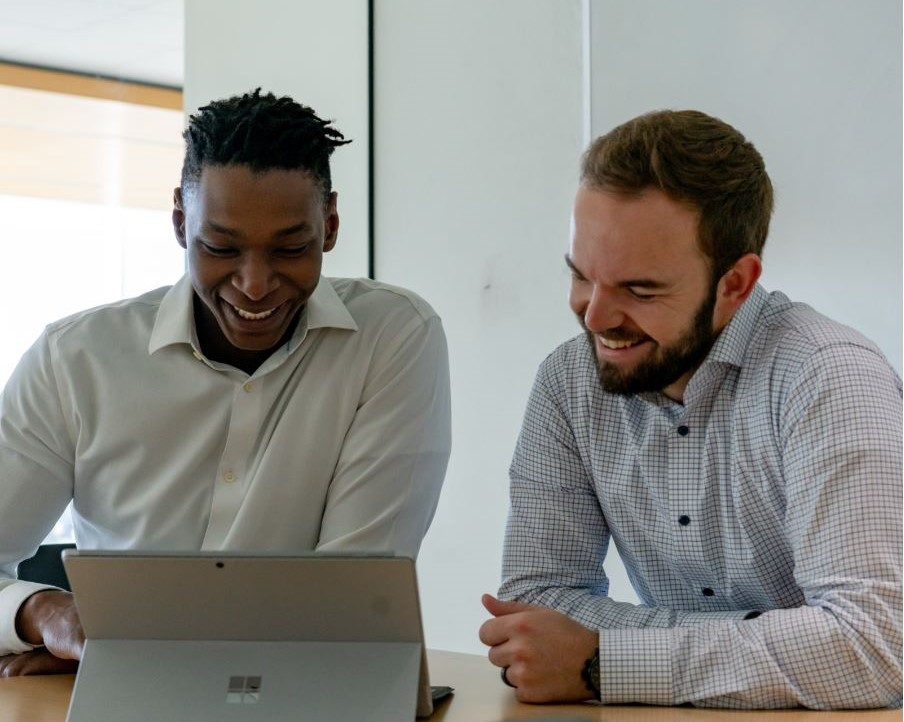 Two men of different ethnicity are smiling and laughing while they work on a computer