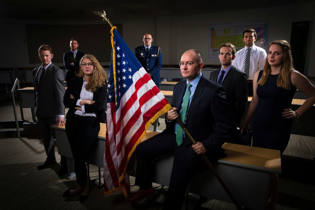 Picture of students and professor sitting in a room gathered around an American Flag