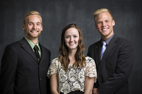 three students dressed in suites