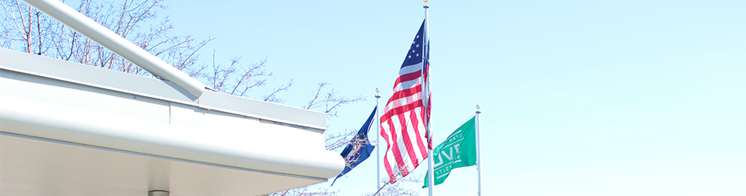 state, country, and uvu flags in front of the business resource center