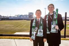 President Holland and Jeff Sermon stand in front of the baseball field