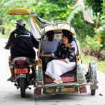 President Tuminez sitting in a rickshaw with someone else