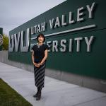 President Tuminez outside wearing a black blouse and skirt standing in front of UVU signage