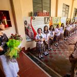 President Tuminez holding a bouquet of flowers while speaking to two lines of children
