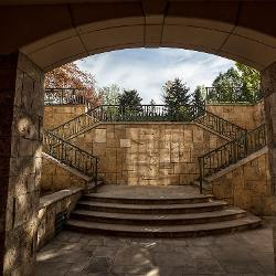 A set of stone stairs lead out from an archway and up to the outdoor pool