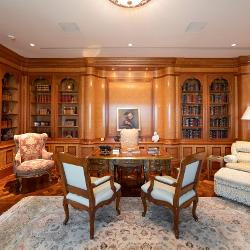 Books and warm wood surround large reading chairs