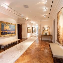 A long hallway of paintings displayed beneath gallery lights