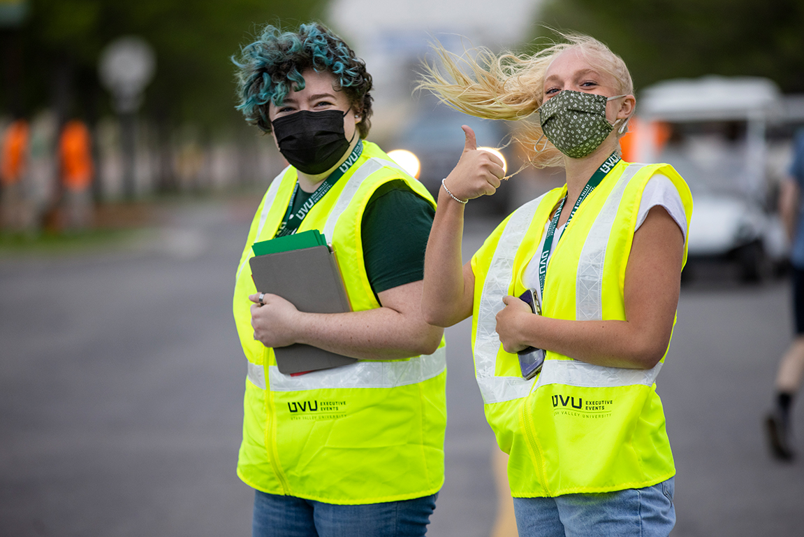 Two event ambassadors in yellow vests help direct parking at commencement. One gives the camera a thumbs up.