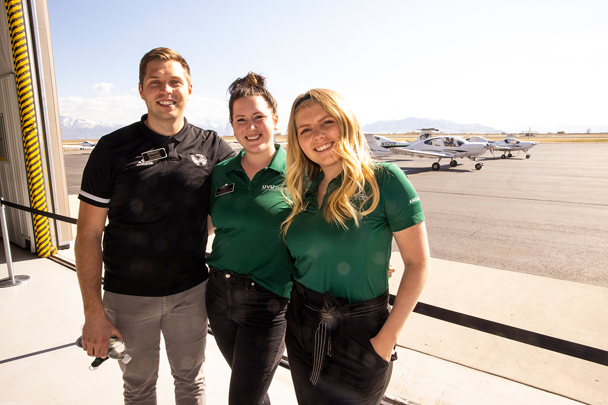 Three event ambassadors smile for the camera at the UVU airport.