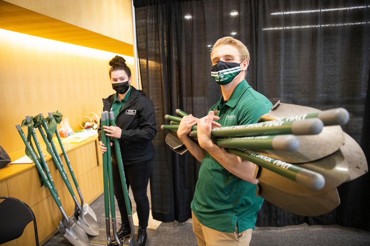 Two event ambassadors prepare shovels for the Alumni House groundbreaking.