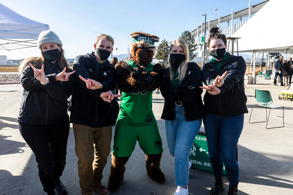 Four event ambassadors stand on either side of Willy the Wolverine mascot and hold up peace signs.