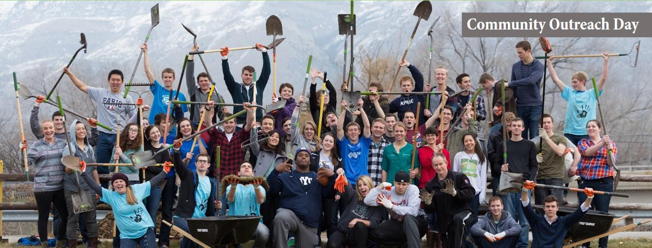 Image of volunteers posing with yard tools, helping with the annual Community Outreach Day service project