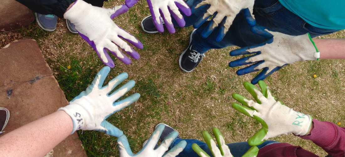 Image of four sets of hands in colorful gloves during a volunteer service project