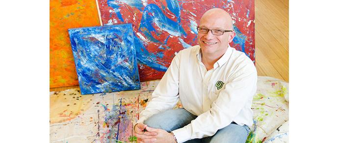 Faculty member posing with artwork